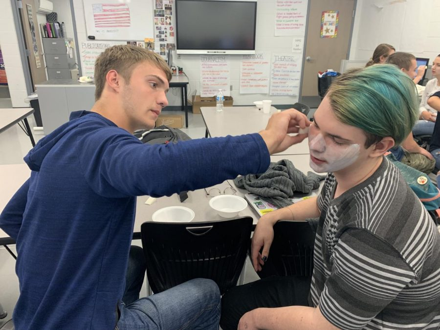Wyatt Norman paints Jericho Brookover's face white.