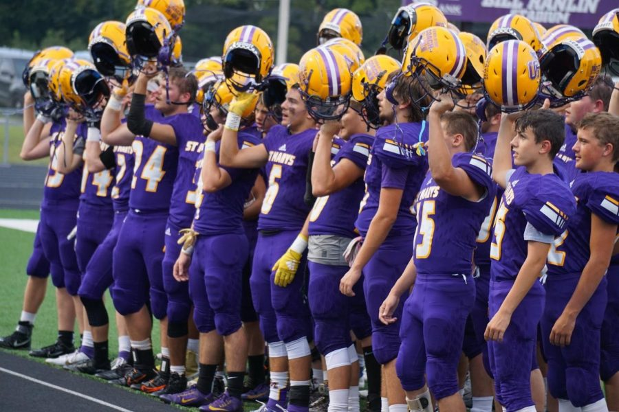 The football team raises their helmets during the first game of the season, while singing the Alma Mater.