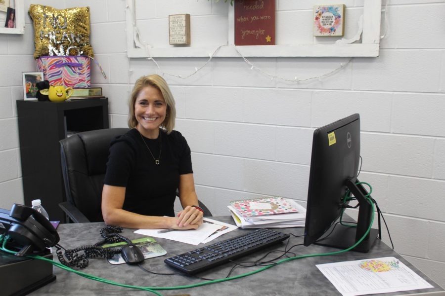 Mrs.Rinard poses for a picture in her office