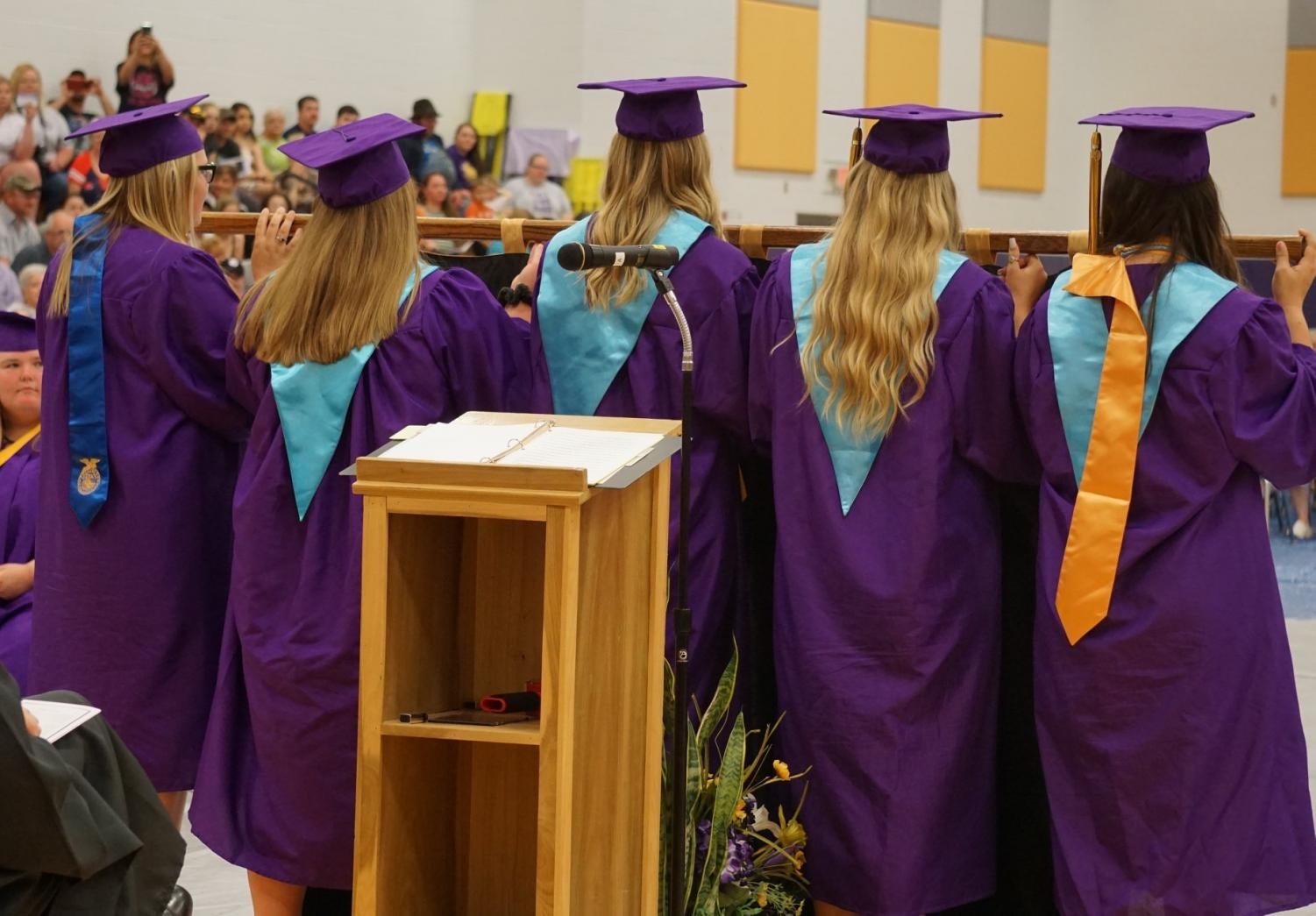 The student body officers carry the class flag during graduation.